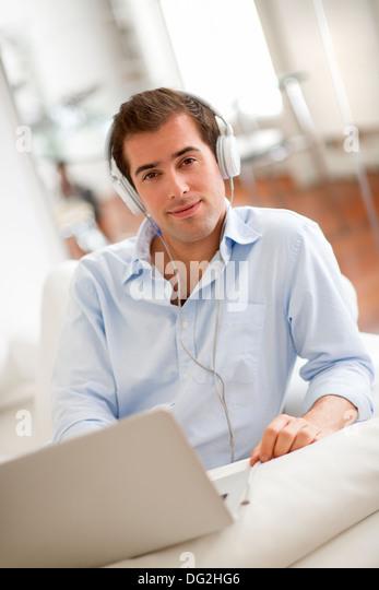 Musikhören mit Kopfhörer auf Laptop-Computer, auf dem Sofa sitzen Mann Stockbild