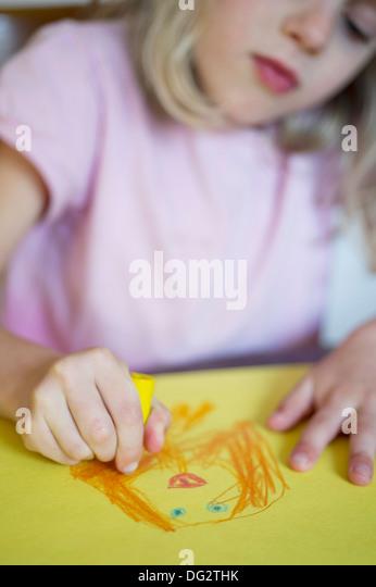 Junges Mädchen Zeichnung auf gelbem Papier Stockbild