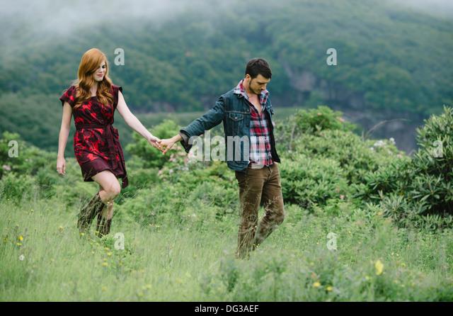 Junges Paar Hand in Hand bei einem Spaziergang durch Feld Stockbild