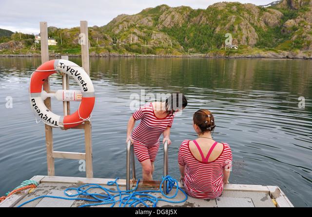 junge Frauen, gekleidet mit einer altmodischen Badehose Baden ins eisige Wasser des Fjords, Hamnøya ich Senja Stockbild