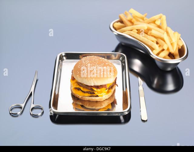 Burger und Pommes frites sitzen in chirurgischen Fächer zur Veranschaulichung ungesunden Ernährung Stockbild