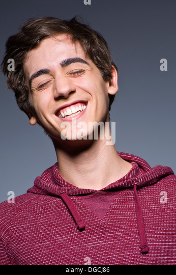 Junger Mann, lachend mit Augen geschlossen, Studioaufnahme Stockbild