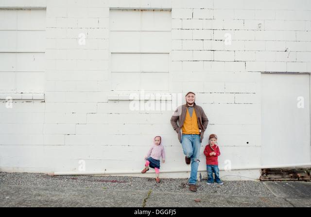 Mitte erwachsener Mann und Sohn und Tochter Wand gelehnt Porträt Stockbild