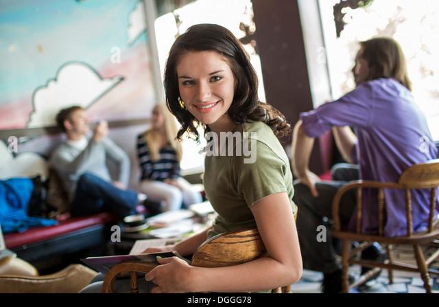 Porträt eines Teenagers im Café mit Studiengruppe Stockbild