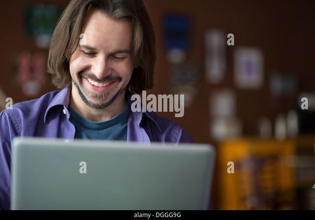 Porträt des jungen Mannes mit am Computer im café Stockbild