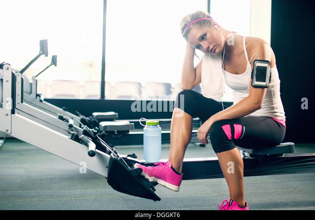Junge Frau, die eine Pause vom Sport im Fitness-Studio Stockbild