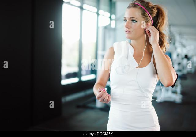 Junge Frau mit Kopfhörern während des Trainings im Fitnessstudio Stockbild