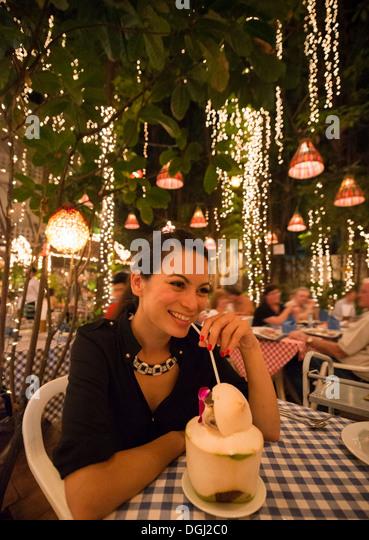 Frau trinkt exotischen Drink im Restaurant unter freiem Himmel Stockbild