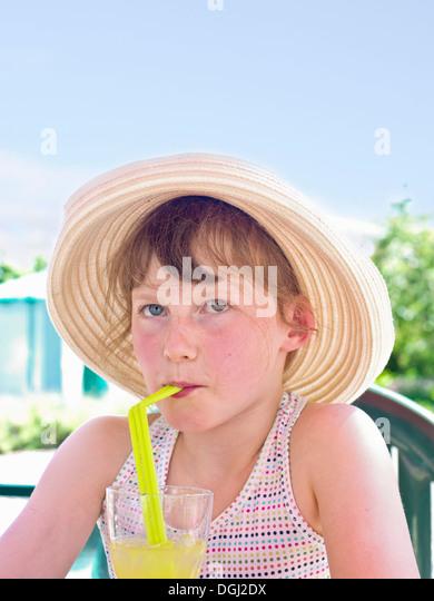 Mädchen tragen Sonnenhut trinken alkoholfreies Getränk Stockbild