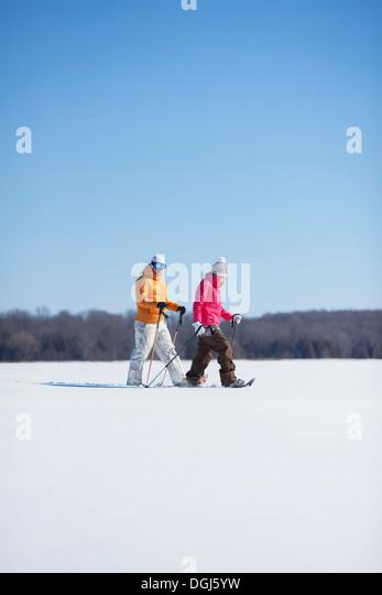 Erwachsene Paare, die auf Schnee Stockbild