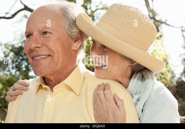 Frau umarmt Mann von hinten Stockbild