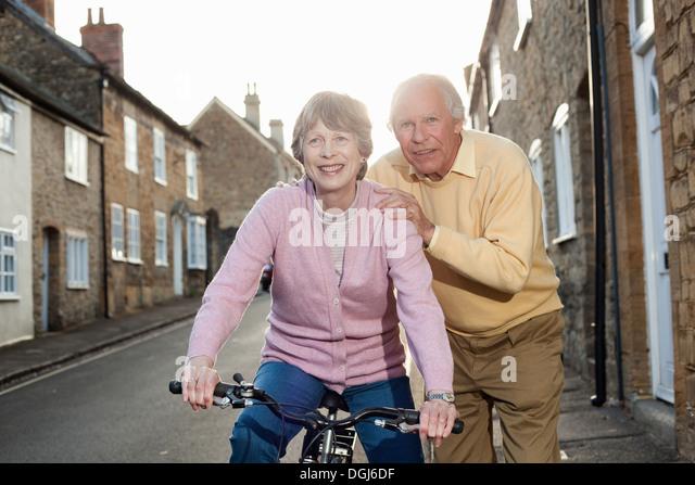 Ehemann tragende Frau auf Fahrrad Stockbild