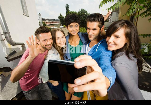 Fünf Freunde fotografieren sich auf Kamera-Handy Stockbild