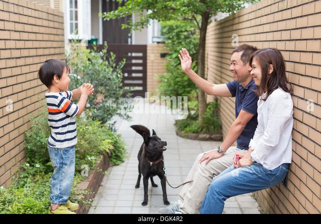 Familie mit Hund, Vater Sohn winken Stockbild