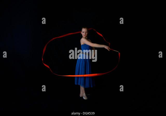 Tänzerin mit Band auf schwarzem Hintergrund Stockbild