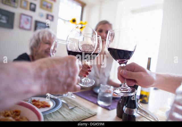 Familie Toasten mit Rotwein am Esstisch Stockbild
