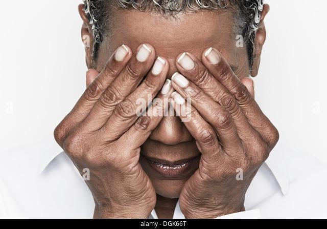 Ältere Frau, die ihre Augen bedecken Stockbild