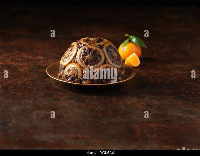 Christmas Pudding mit in Scheiben geschnittenen Orangen verziert Stockbild