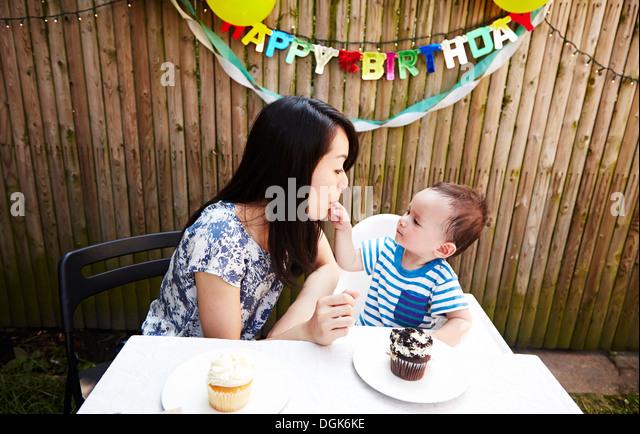 Baby Boy indem Finger in Mutters Mund Stockbild