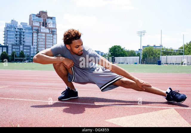Junger Mann Dehnung Bein auf Laufband Stockbild