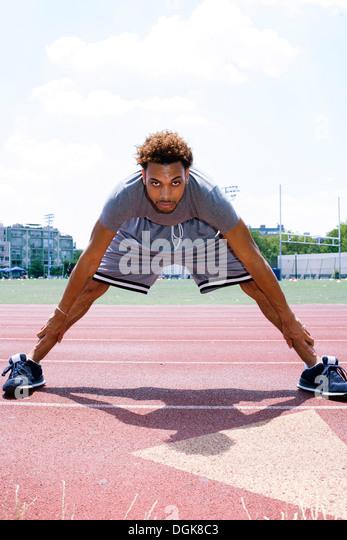 Junger Mann stretching auf Laufschiene Stockbild