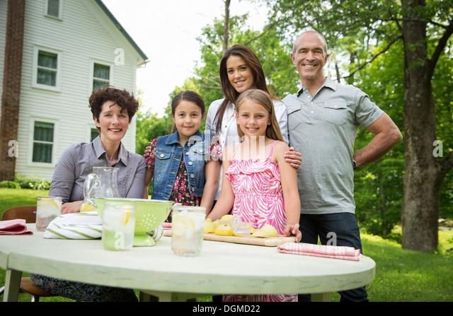 Ein Sommer-Familientreffen auf einem Bauernhof. Fünf Menschen posieren neben dem Tisch, wo ein Kind frische Stockbild