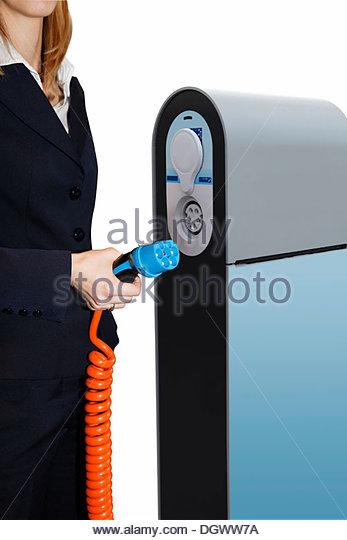 Frau mit einem elektrischen Kabel an eine Ladestation für Elektroautos Stockbild