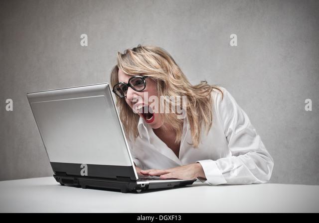 Böse blonde Frau schreiend gegen einen laptop Stockbild
