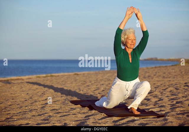 Ältere Frau praktizieren Yoga-Posen am Sandstrand. Ältere kaukasischen Frau Dehnung der Beine und Arme Stockbild