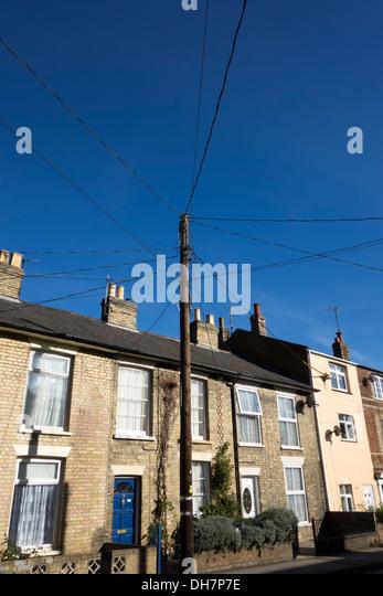 Aufwand Stromkabel aus einer zentralen Holzstab zu einer Reihe von Reihenhäusern in Sudbury, Suffolk, England. Stockbild