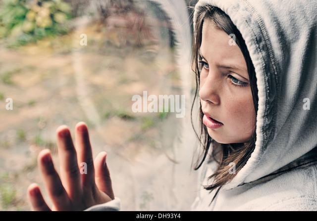 Junge Mädchen Blick aus Fenster Stockbild