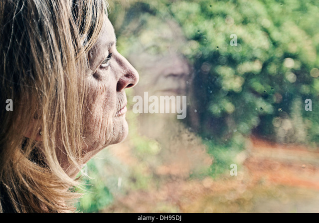 Senior Lady Blick aus Fenster Stockbild