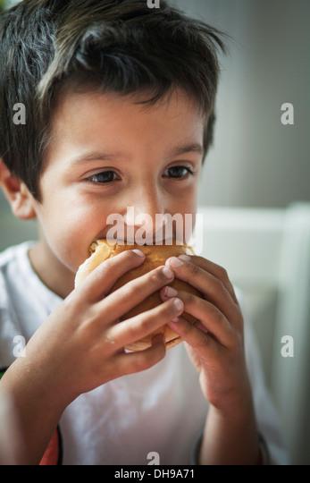 Kind einen Burger Essen Stockbild