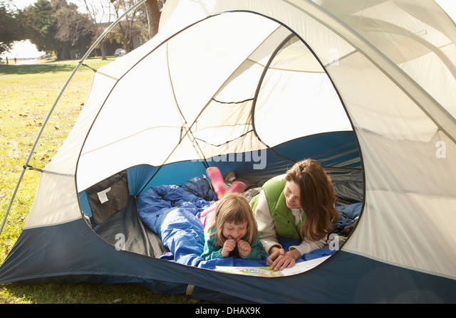 Eine Mutter und Tochter lag In einem Zelt ein Buch zu lesen; Crab Cove, Alemada, California, Vereinigte Staaten Stockbild