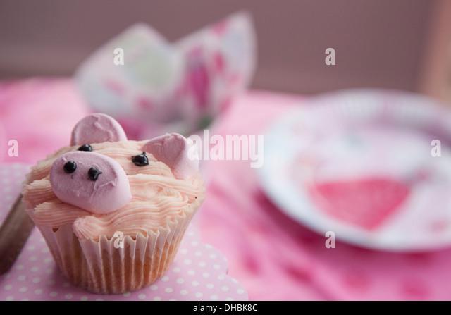 Eine Partei, mit einem rosa Tuch und einen Cupcake Geburtstagstisch mit dem Bild eines Schweins. Stockbild