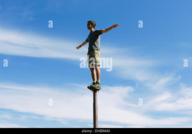 Mann stehend balancieren auf Metallpfosten mit Blick auf weitläufige Himmel auf Überraschung Gebirge alpinen Stockbild