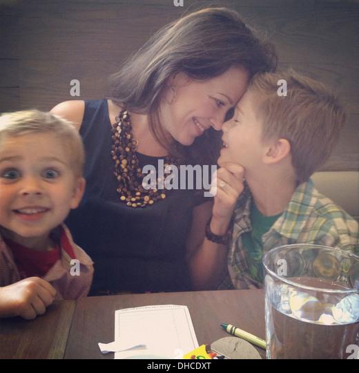 Glückliche Mutter und zwei Söhne am Tisch im Restaurant Stockbild