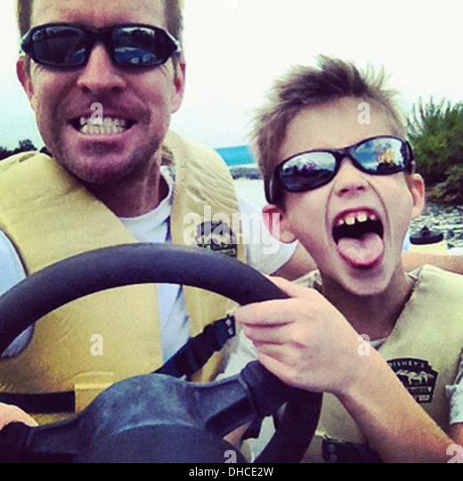 Vater und Sohn Spaß Steuer des Bootes, Close Up Stockbild