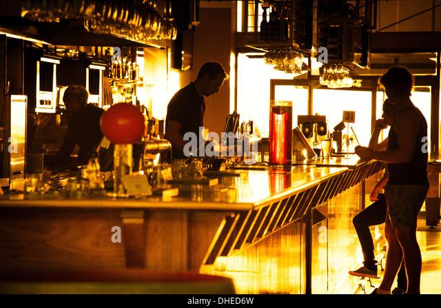Mitarbeiter und Förderer einer Glenelg Bar (in Adelaide) Silhouette gegen den Sonnenuntergang. Stockbild