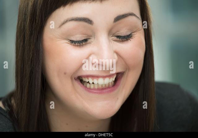Junge Frau lachen, Augen geschlossen Stockbild