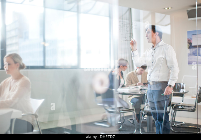 Mann schreiben an Glaswand, Kolleginnen und Kollegen im Hintergrund Stockbild