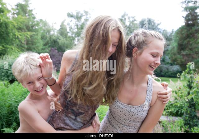 Jungen und Mädchen im Teenageralter spielen kämpfen im Garten Stockbild