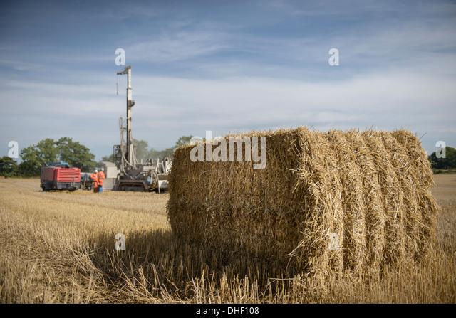 Bohranlage in Feld mit Heuballen im Vordergrund Stockbild