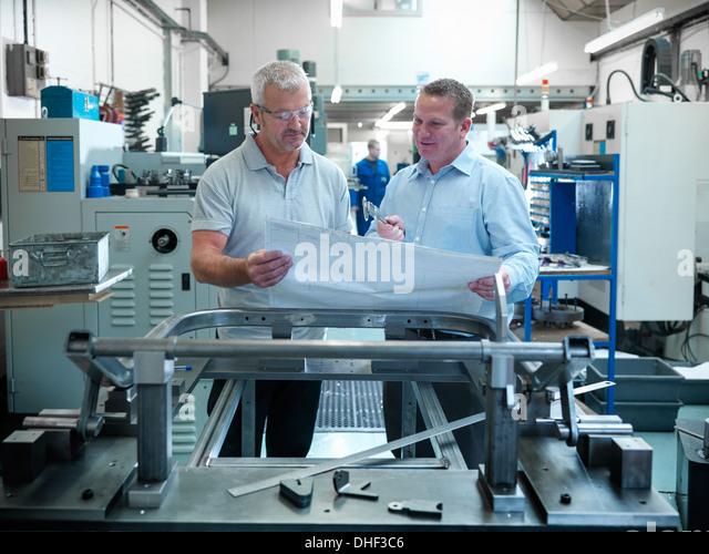 Ingenieure prüfen Pläne in Fabrik Stockbild