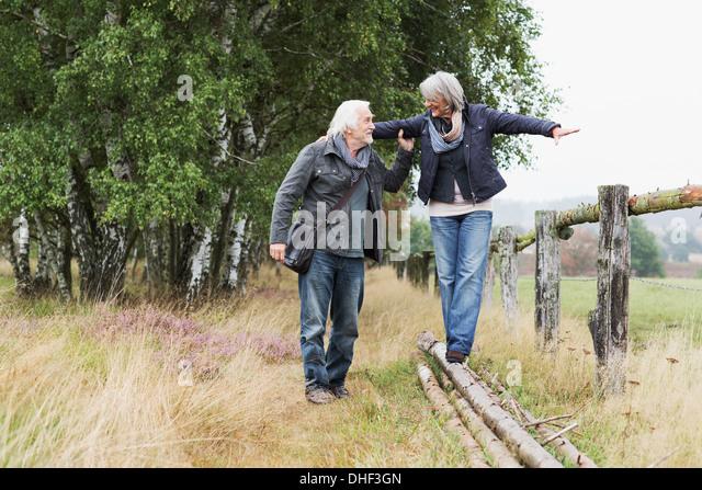 Älteres Paar, Frau balancieren auf Protokolle Stockbild