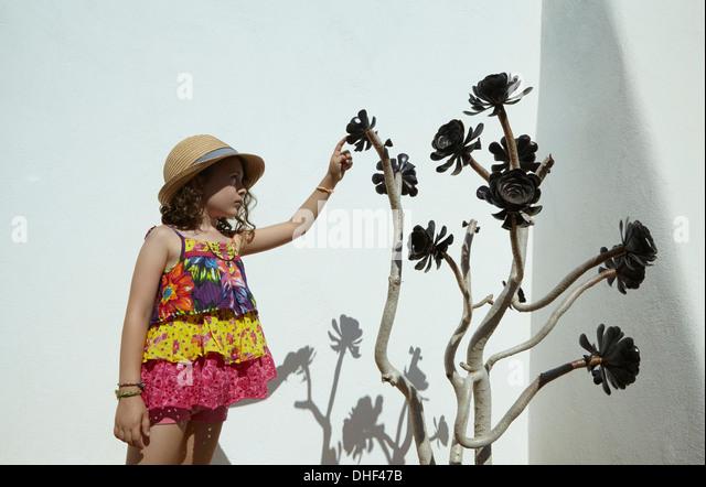 Mädchen, die exotische Pflanze zu berühren Stockbild