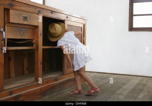 Mädchen auf der Suche unter Schrank Stockbild