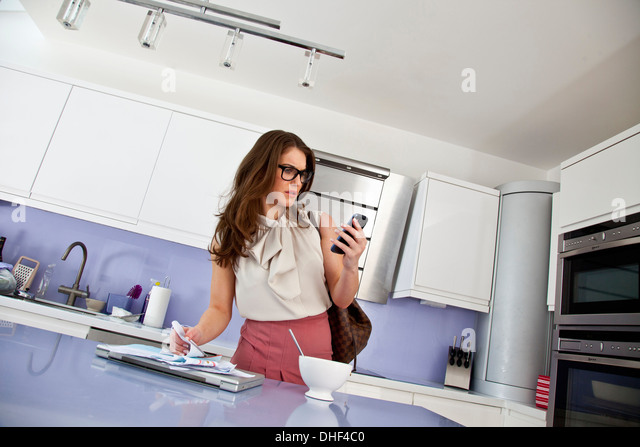 Junge Frau mit Handy und Papierkram beim Frühstück Stockbild