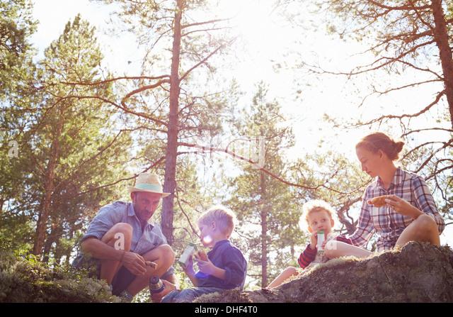 Familie Picknick auf Felsen sitzend Stockbild