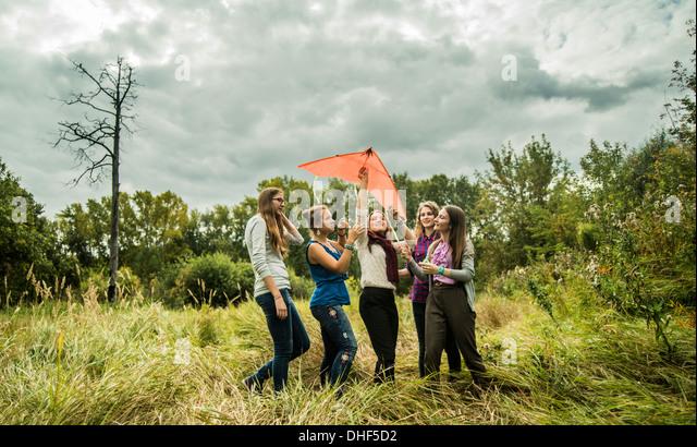 Fünf junge Frauen mit Drachen im Buschland Stockbild